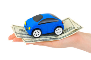 Hand with money and toy car isolated on white background